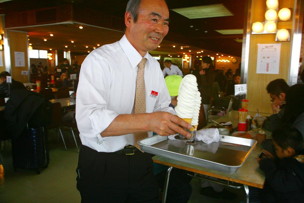 笑顔でソフトクリームを運ぶスタッフ